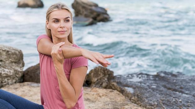 Mooie blonde vrouw die zich uitstrekt op het strand