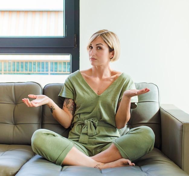 Mooie blonde vrouw die zich verbaasd en verward voelt, onzeker over het juiste antwoord of de juiste beslissing, probeert een keuze te maken