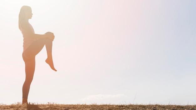 Mooie blonde vrouw doet yoga buitenshuis