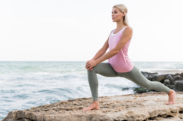 Mooie blonde vrouw doet yoga op het strand