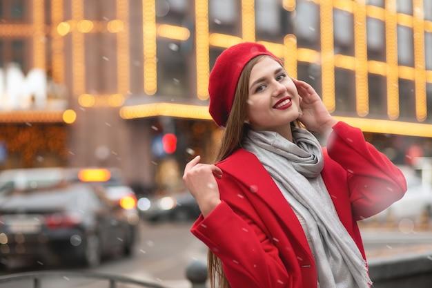 Mooie blonde vrouw draagt rode baret en winterjas poseren in de stad met nieuwjaarsdecor. ruimte voor tekst