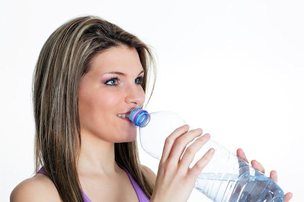 Mooie blonde vrouw drinkwater na sport