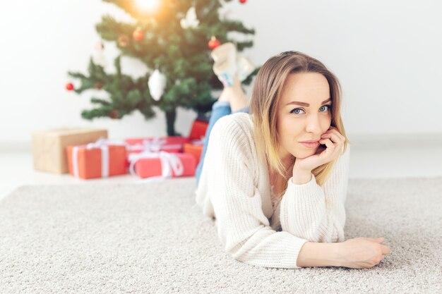 Mooie blonde vrouw, gekleed in een warme gebreide trui, liggend op een tapijt in de buurt van versierde kerstboom in een woonkamer. veel cadeautjes onder de boom.