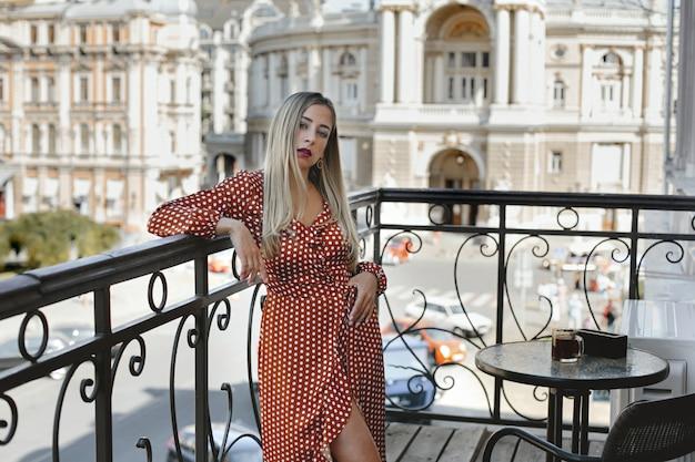 Mooie blonde vrouw gekleed in lange rode polka dot jurk staat op het terras bij de salontafel met uitzicht op de straat van de stad met oude architectonische gebouwen