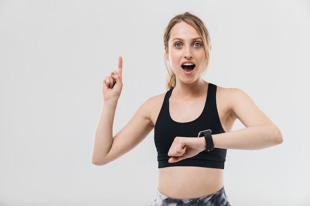 Mooie blonde vrouw gekleed in sportkleding trainen en kijken naar polshorloge tijdens fitness in sportschool geïsoleerd over witte muur