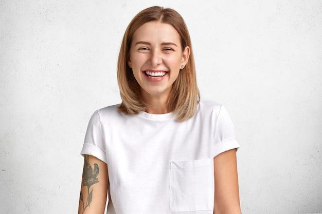 Mooie blonde vrouw, gekleed in wit t-shirt