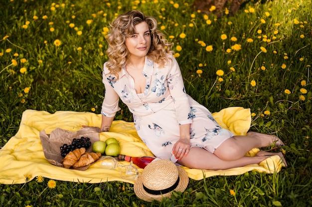 Mooie blonde vrouw - gelukkige levensstijl, weekendje uit voor een wandeling in een picknickpark in de zomertuin, model zit op plaid met eten - zomerweer