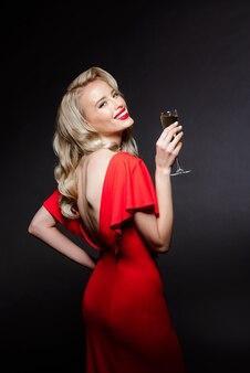 Mooie blonde vrouw in avondjurk glimlachen, die champagneglas houdt
