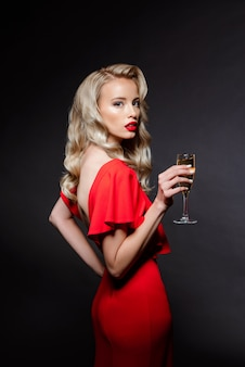 Mooie blonde vrouw in avondjurk poseren, champagne glas te houden