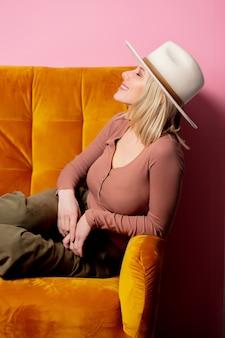 Mooie blonde vrouw in cowboyhoed zitten in een vintage fauteuil op roze muur