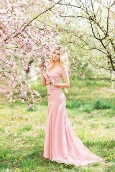 Mooie blonde vrouw in een roze lange jurk in een lente bloeiende tuin