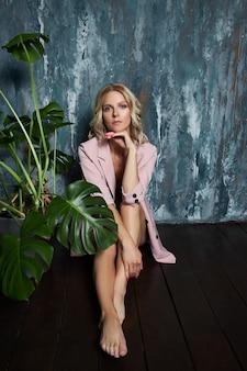 Mooie blonde vrouw in een sexy roze jasje.