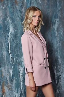Mooie blonde vrouw in een sexy roze jasje
