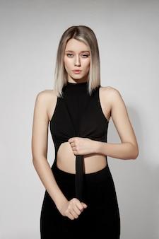Mooie blonde vrouw in een strakke zwarte jurk. vrouw intieme problemen, complexen