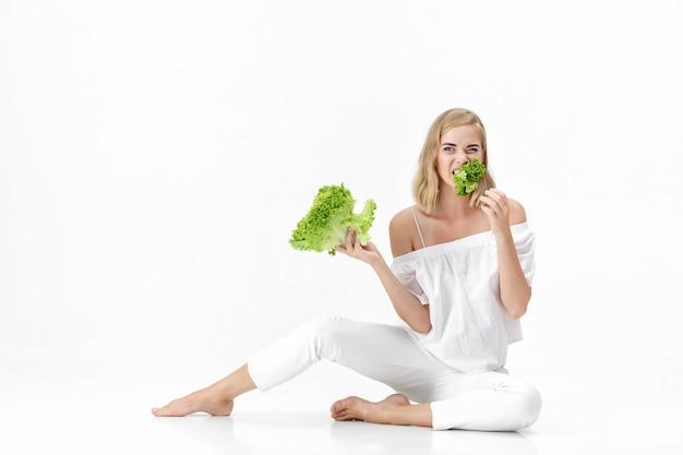 Mooie blonde vrouw in een witte blouse die een verse groene salade op een witte achtergrond eet. gezondheid en voeding