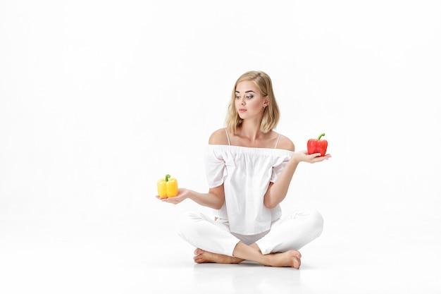Mooie blonde vrouw in een witte blouse kiest voor een gele of rode paprika. gezondheid en voeding