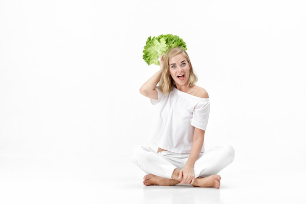 Mooie blonde vrouw in een witte blouse met een frisse groene salade op een witte achtergrond. gezondheid en voeding