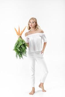 Mooie blonde vrouw in een witte blouse met een verse wortel met groene bladeren op een witte achtergrond. gezondheid en voeding