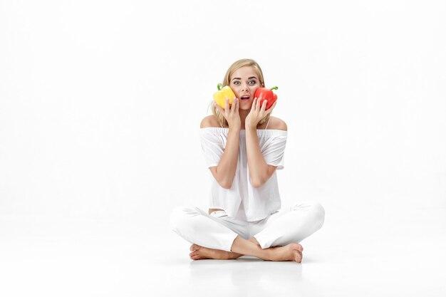 Mooie blonde vrouw in een witte blouse met gele en rode paprika. gezonde voeding en voeding