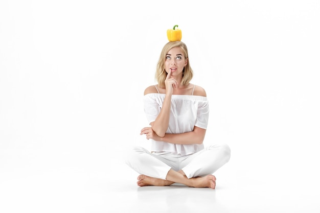Mooie blonde vrouw in een witte blouse met gele paprika. gezonde voeding en voeding