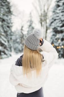Mooie blonde vrouw in een witte jas op zoek naar het winterbos