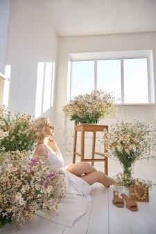 Mooie blonde vrouw in een witte jurk zit op de vloer tussen de kamillebloemen