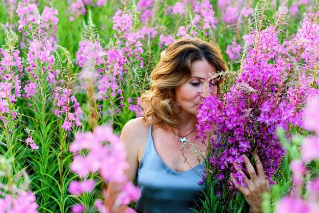 Mooie blonde vrouw in grijze jurk ontspant met bos bloemen op wilgenroosje weide