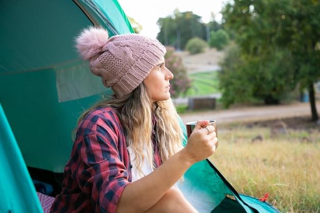 Mooie blonde vrouw in hoed die thee drinkt, in tent zit en op landschap kijkt. kaukasische langharige dame die in stadspark kampeert. toerisme, reis en levensstijlconcept