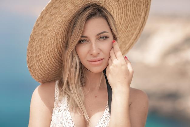 Mooie blonde vrouw in hoed op zee kust achtergrond.