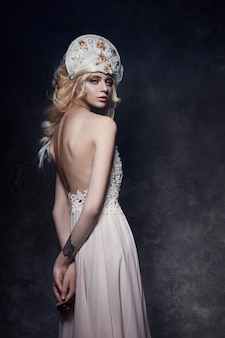 Mooie blonde vrouw in jurk met blote rug en een tiara op haar hoofd