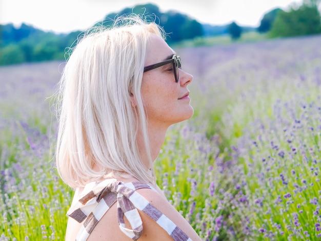 Mooie blonde vrouw in jurk zitten tussen lavendelvelden in de provence. violette lavendelvelden die in de zomerzonlicht bloeien. zee van lila bloemen landschap. stelletje geurende bloemen uit de franse provence