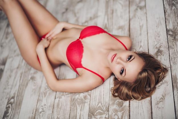 Mooie blonde vrouw in lingerie liggend op houten vloer
