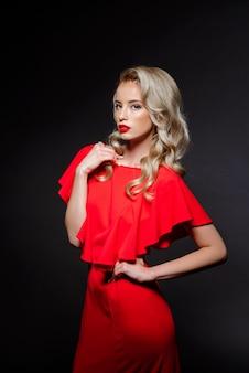 Mooie blonde vrouw in rode avondjurk