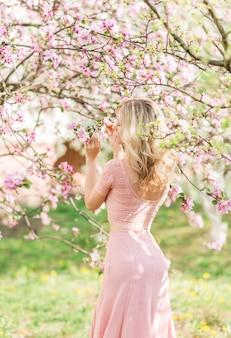 Mooie blonde vrouw in roze bloemen. lentetuin in de zon