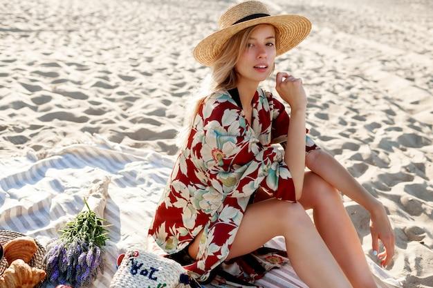 Mooie blonde vrouw in strooien hoed zittend op tropisch strand, genieten van vakantie in de buurt van de oceaan.