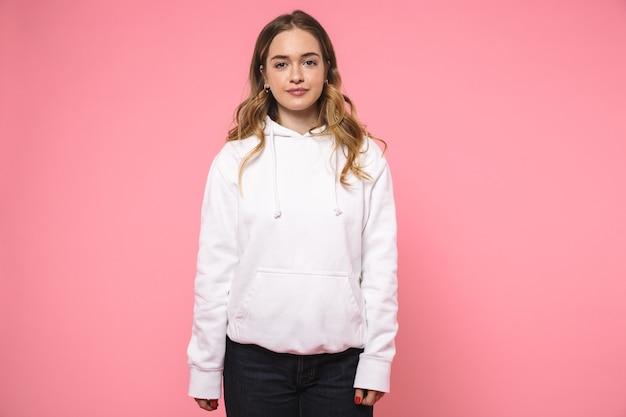 Mooie blonde vrouw in vrijetijdskleding poseren en kijken naar de voorkant over roze muur