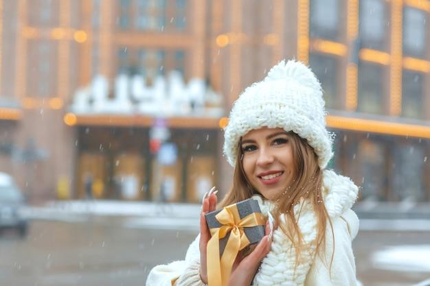 Mooie blonde vrouw in witte jas met een geschenkdoos op straat tijdens de sneeuwval. ruimte voor tekst