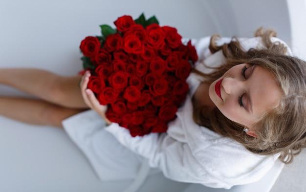 Mooie blonde vrouw in witte jurk met boeket van rode rozen studio. gelukkig meisje met rode rozen