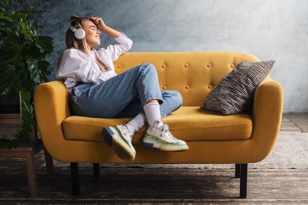 Mooie blonde vrouw in witte koptelefoon zit op gele sofand geniet van het luisteren naar muziek.