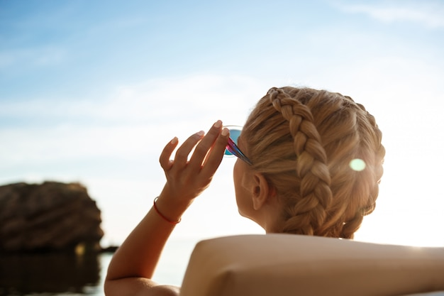 Mooie blonde vrouw in zonnebril die dichtbij overzees zonnebaadt