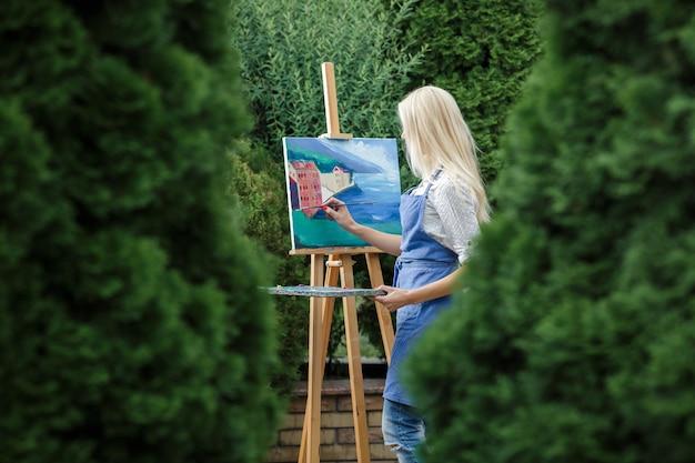 Mooie blonde vrouw kunstenaar met een borstel in haar hand tekent op canvas in de tuin.