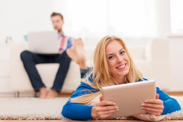 Mooie blonde vrouw met behulp van digitale tablet en ontspannen op capet thuis