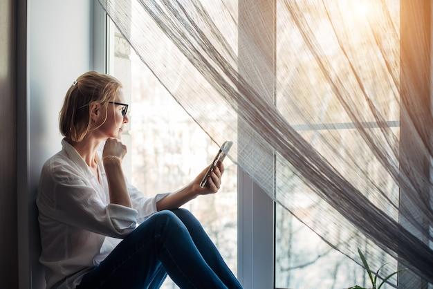 Mooie blonde vrouw met blote voeten in een bril, jeans en wit overhemd zittend op de vensterbank in zonlicht, smartphone in haar hand houden. ontspanning in een gezellig interieur. zijaanzicht, close-up.