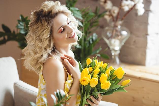 Mooie blonde vrouw met boeket gele tulpen