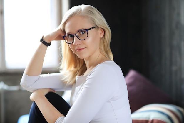 Mooie blonde vrouw met bril poseren in wit overhemd