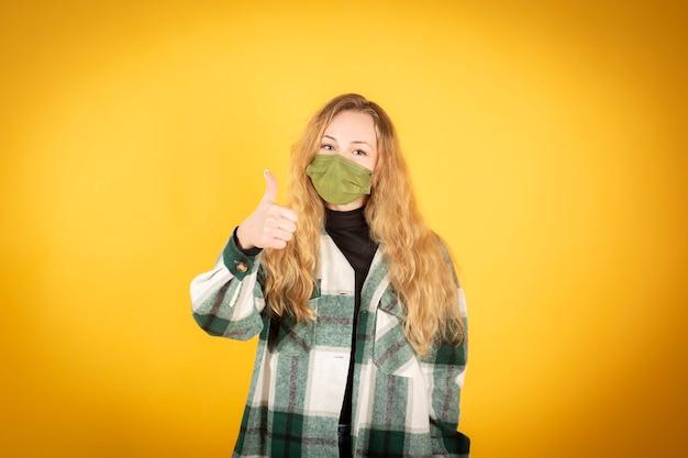 Mooie blonde vrouw met chirurgisch masker op gele achtergrond, ok met haar hand