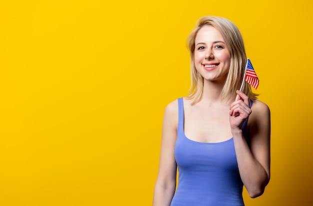 Mooie blonde vrouw met de vlag van de vs op gele muur