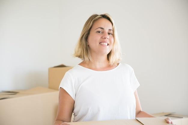 Mooie blonde vrouw met doos in nieuw huis of appartement
