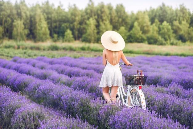 Mooie blonde vrouw met een fiets in lavendel. uitzicht vanaf de achterkant.