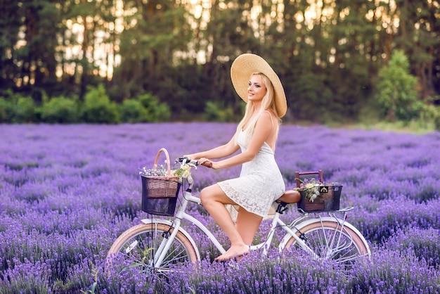 Mooie blonde vrouw met een fiets in lavendel.